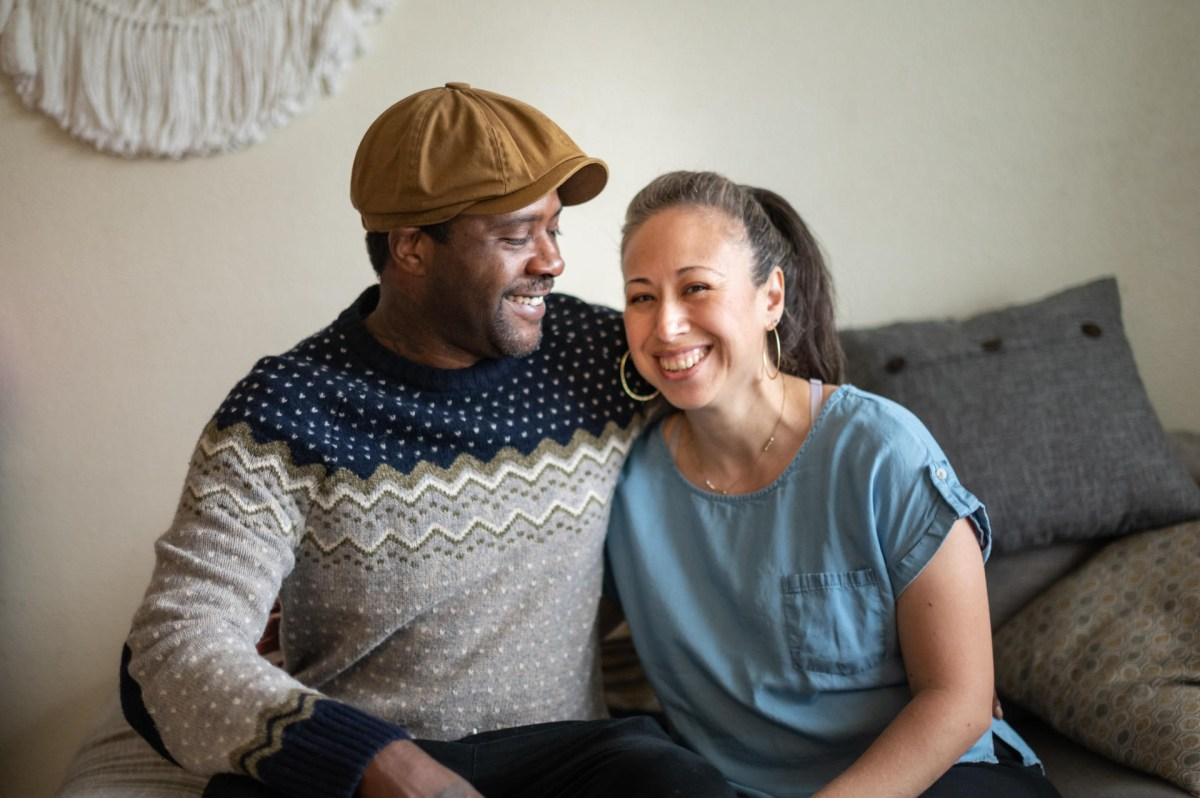 Kris Walker embraces his wife as they sit next to each other on a couch.