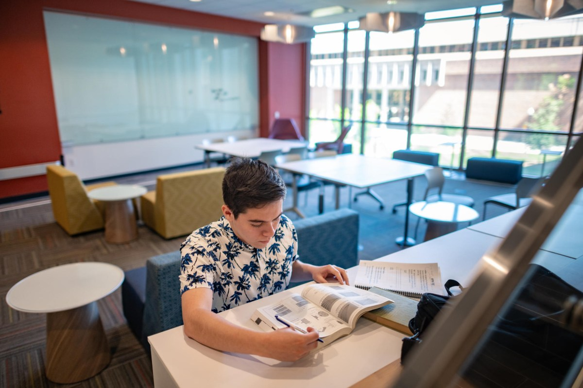 A student sits at a raised counter in a group seating area in the new Science Building.