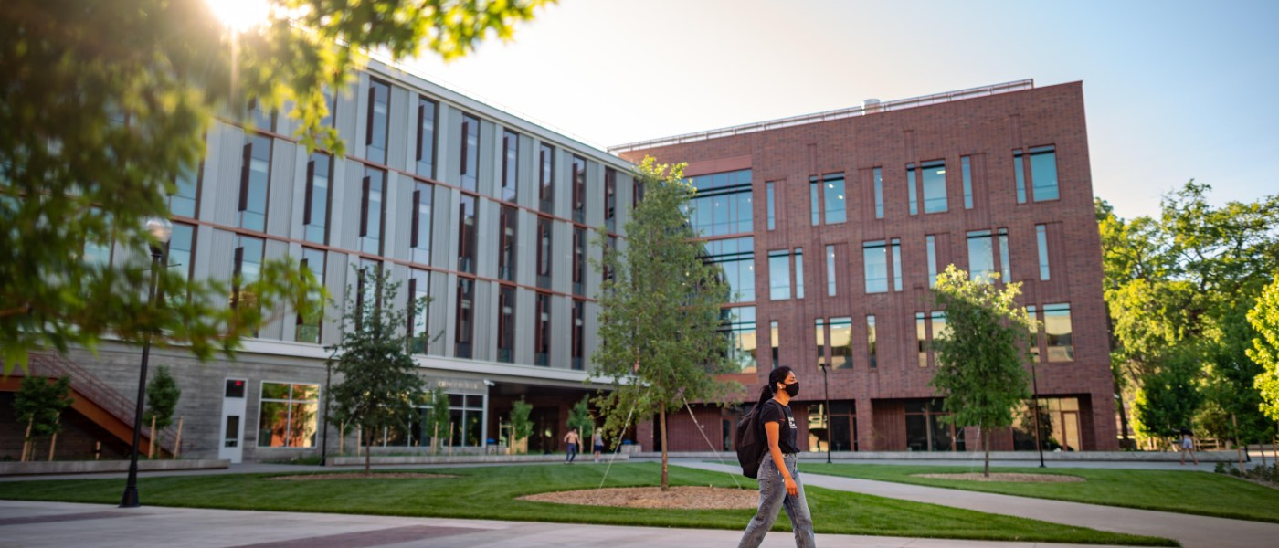 A student walks past the Science Building in the evening light.