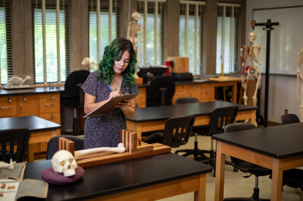 Daisy Linsangan writes on a clipboard near a table with model human remains.