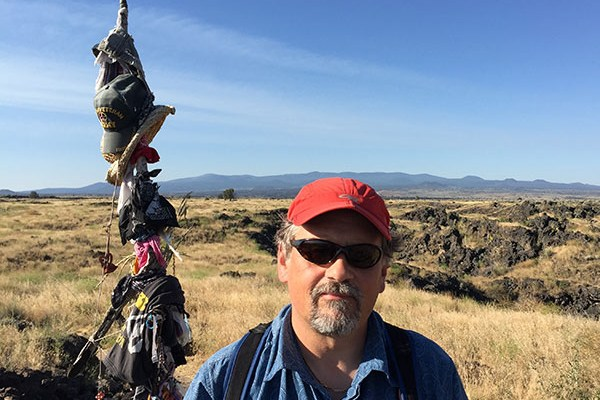 Jesse Dizard stands on an open ridge in the foothills in front of a wooden pole with clothes and hats hanging from it.