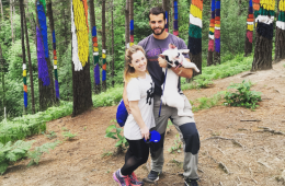 Lindsay Woychick, her husband, and french bulldog pose in a colorful forest in Spain.
