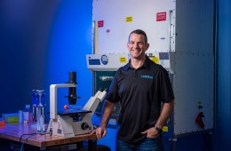 John Aylworth poses and smiles amongst scientific equipment