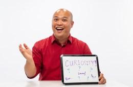 """Eduardo Europa holds a sign that says """"curiosity."""""""