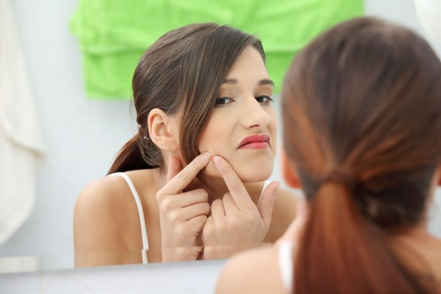 Woman looking at the mirror to get rid of her pimples