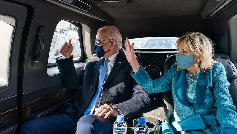 President Joe Biden and First Lady Dr. Jill Biden wave as they ride in the Presidential limousine Wednesday