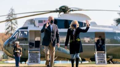President Joe Biden and First Lady Jill Biden wave as they walk across the South Lawn of the White House after disembarking Marine One Sunday