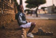 African boy sitting on dirt