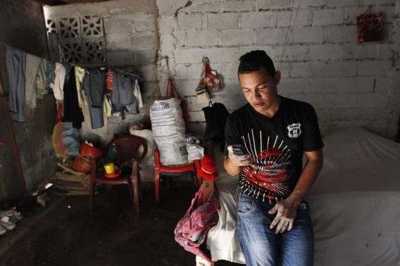 Victor Toruno looks at his mobile phone at his home, which also serves as a bakery, in the Hialeah neighborhood in Managua August 13, 2014.   REUTERS/Oswaldo Rivas