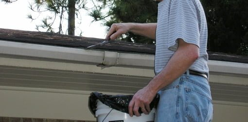 Using a garden trowel to clean gutters