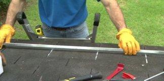 Installing a sheet metal rain diverter on a roof.