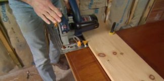 Using circular saw on clamped board guide to trim door bottom.