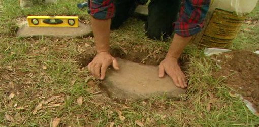 Allen Lyle laying a stepping stone path.