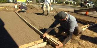 Using screed board to level concrete in forms