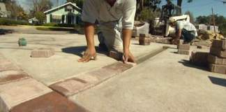 Pavers being laid as accents on a poured concrete driveway
