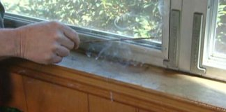 Holding lit incense stick next to window to check for air leaks
