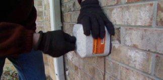 Putting foam cover over outdoor spigot.