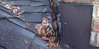 Leaking roof flashing around a chimney full of leaves