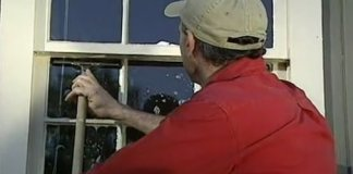 Cleaning small window panes with a custom modified squeegee.