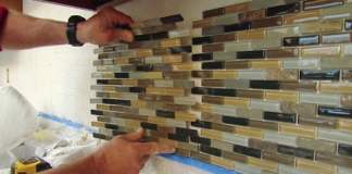 Installing a sheet of mosaic tile on a kitchen backsplash.