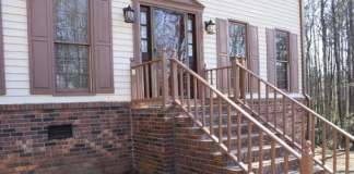 Entry to house after makeover with repaired railings, new door, and lighting.