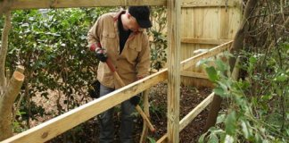 Danny Lipford working on building a pressure treated wood privacy fence.
