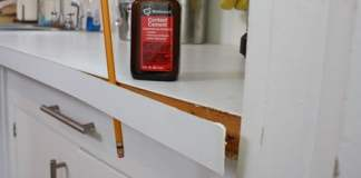 Using a pencil to hold plastic laminate edging away from countertop while contact cement dries.