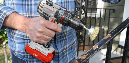 Removing rust on wrought iron with a wire brush drill attachment.