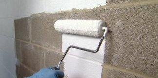 Rolling masonry sealer on basement walls.