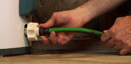 Attaching a garden hose to drain valve on hot water heater.