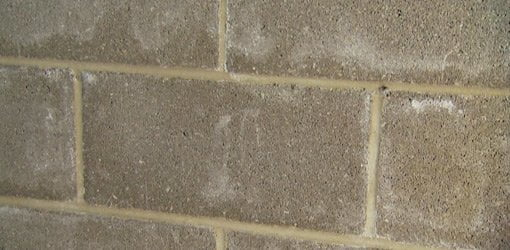 White efflorescence stains on concrete block wall.