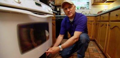 Joe Truini using a coat hanger wire to clean between oven door glass.