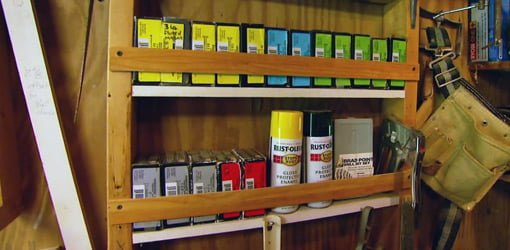 Shelves in open stud wall in a workshop filled with nail and screw boxes, spray paint cans, and hand tools..
