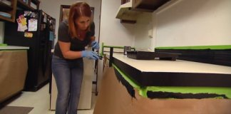 Woman rolling black paint on plastic laminate kitchen countertops.