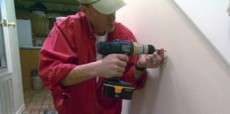Using a cordless drill to attach drywall screws to drywall wall.