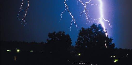 Lightning striking tree at night.
