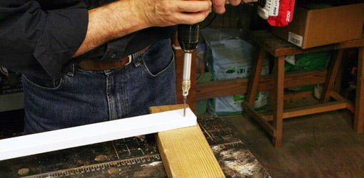 Drilling a pilot hole in a wood board.