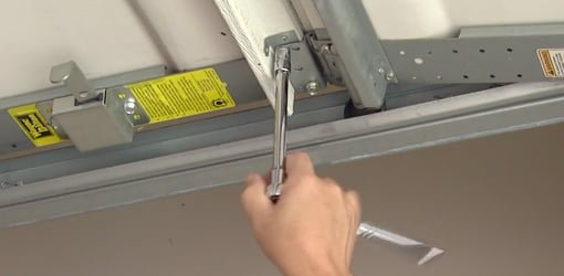 Using socket wrench to tighten a loose bolt on garage door.