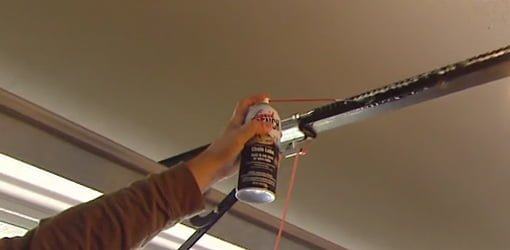 Using spray lubricant to lubricate the track on a garage door.