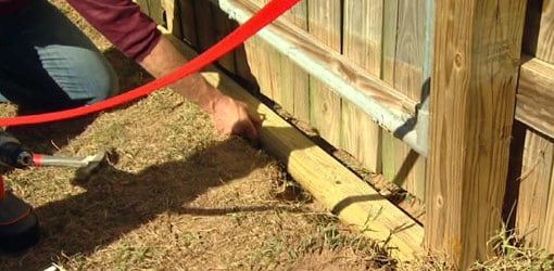 Installing wood to prevent dogs from digging under a gate