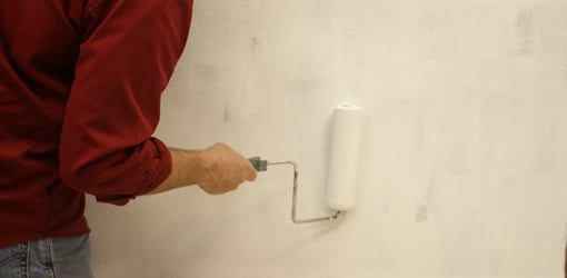 Rolling stain blocking primer over a dark wall.