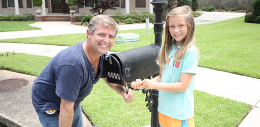 Allen Lyle and Madison Faust standing by repaired and painted mailbox.