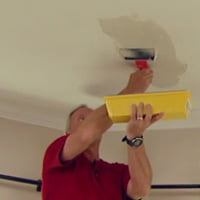 Danny Lipford applying drywall joint compound to ceiling.