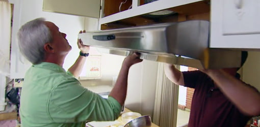 Danny Lipford and Tom Blizzard installing a new kitchen range hood.
