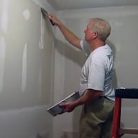 Man applying joint compound to drywall.