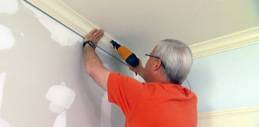 Using a pneumatic nailer to attach crown molding.