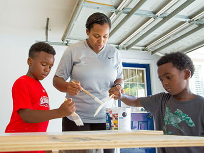 Shar'Day and two of her sons paint the shelving.