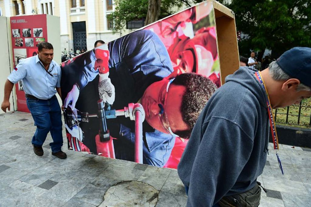 "Venezuelan National Assembly employees remove from the building  pictures of late President Hugo Chavez, in Caracas on January 6, 2016. Venezuela's opposition on Tuesday broke the government's 17-year grip on the legislature and vowed to force out President Nicolas Maduro despite failing for the time being to clinch its hoped-for ""supermajority."" AFP PHOTO/RONALDO SCHEMIDT / AFP / RONALDO SCHEMIDT"