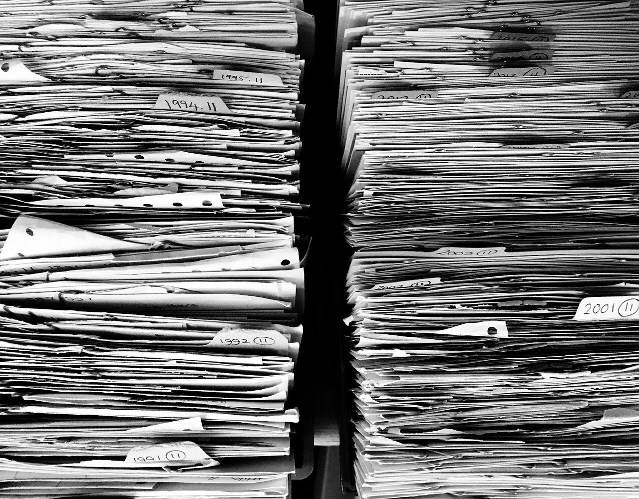 Two stack of paper and files representing too much work