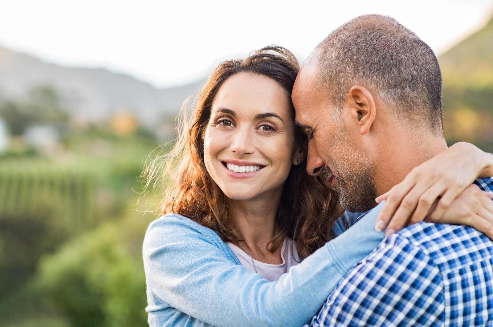 Mature romantic couple embracing outdoor. Happy woman embracing